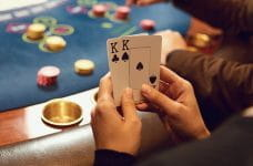 A woman holding two playing cards.