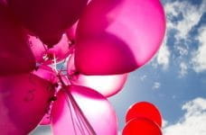 Pink balloons against a blue sky.