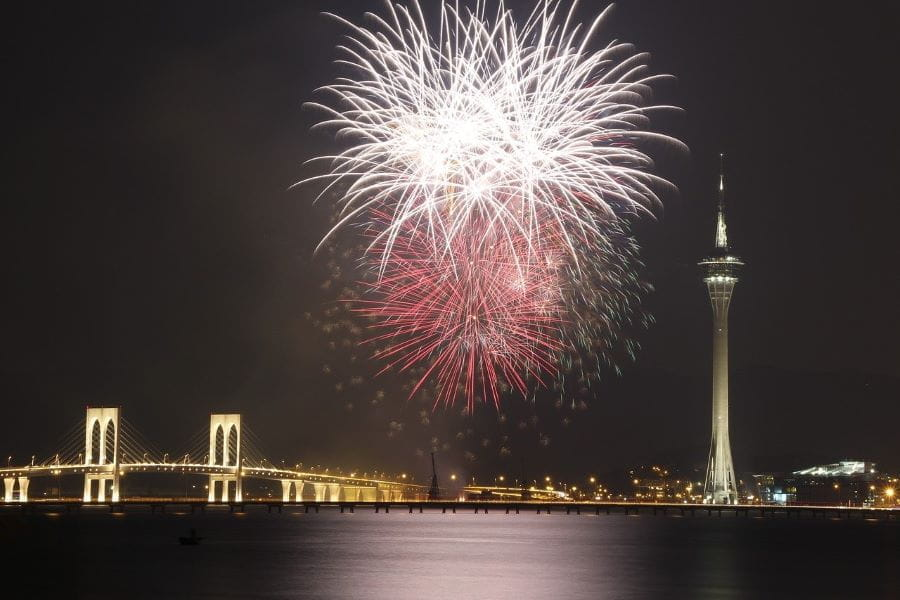 Fireworks going off over Macau at night with a tower and a bridge in the background.