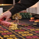 A croupier moving chips on a roulette table.