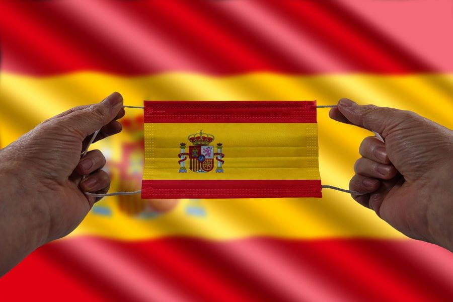 A pair of hands hold a mask with the Spanish flag on it in front of a Spanish flag.