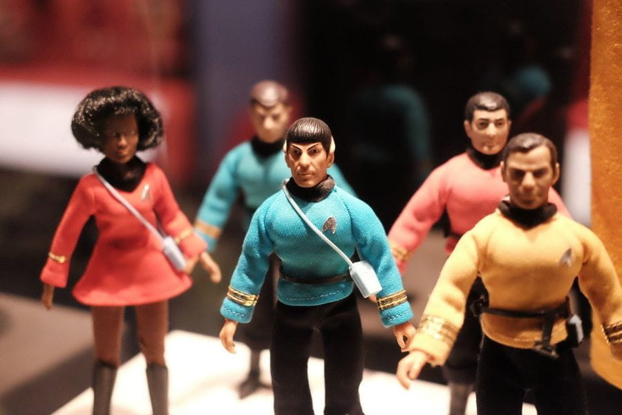 A row of Star Trek action figures stand on a desk.