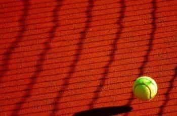 A tennis ball bouncing on a clay tennis court.