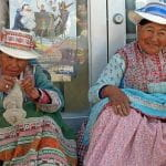 Two older women sit on a stoop in Chivay, Peru wearing traditional costumes.
