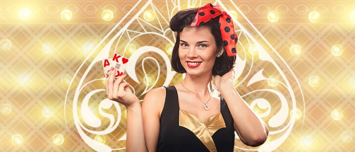 A female casino dealer, wearing a bow in her hair, holding playing cards.
