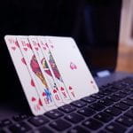 Four playing cards lean against an open laptop's screen.