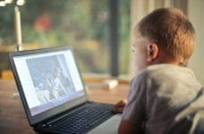 A child watching a video on a laptop.