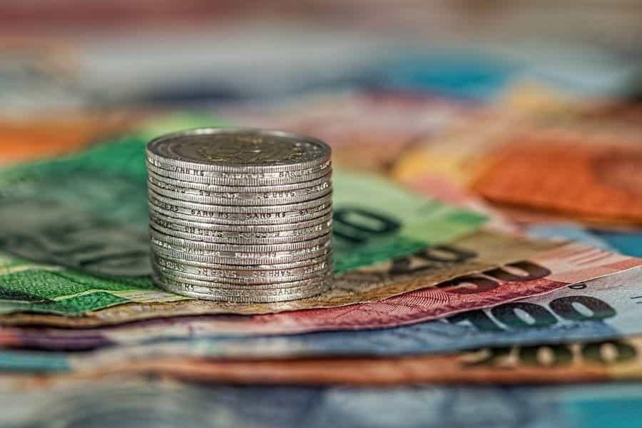 Setumpuk kecil koin di atas beberapa uang kertas.