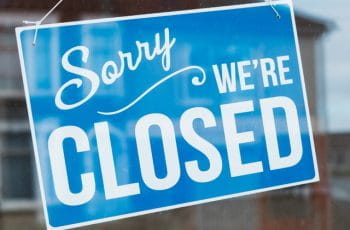 A blue shop sign, reading 'sorry we're closed'.