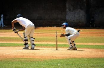 Two people playing cricket on a cricket field.