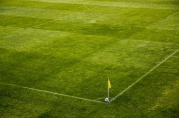 A yellow corner flag and football on a pitch.