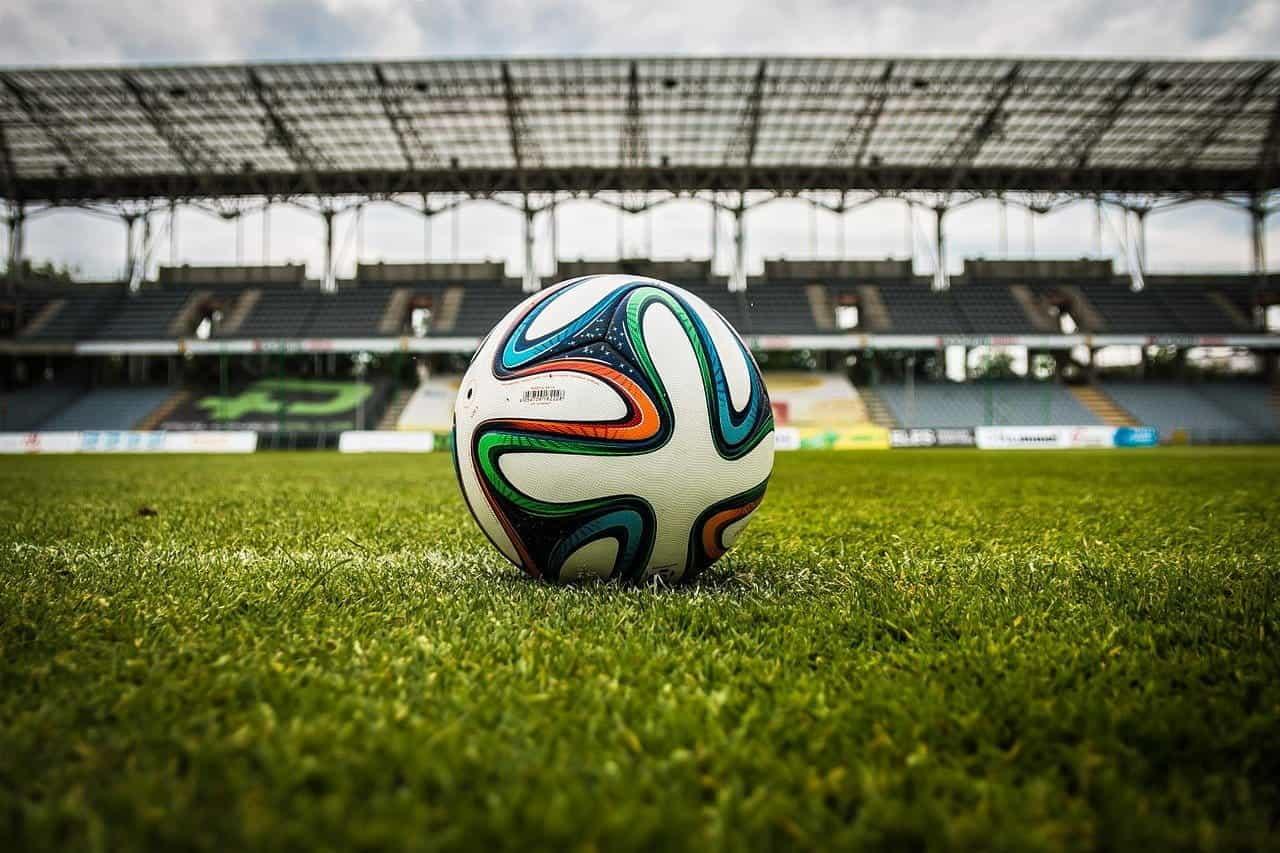 Sepak bola di lapangan di depan tribun kosong.