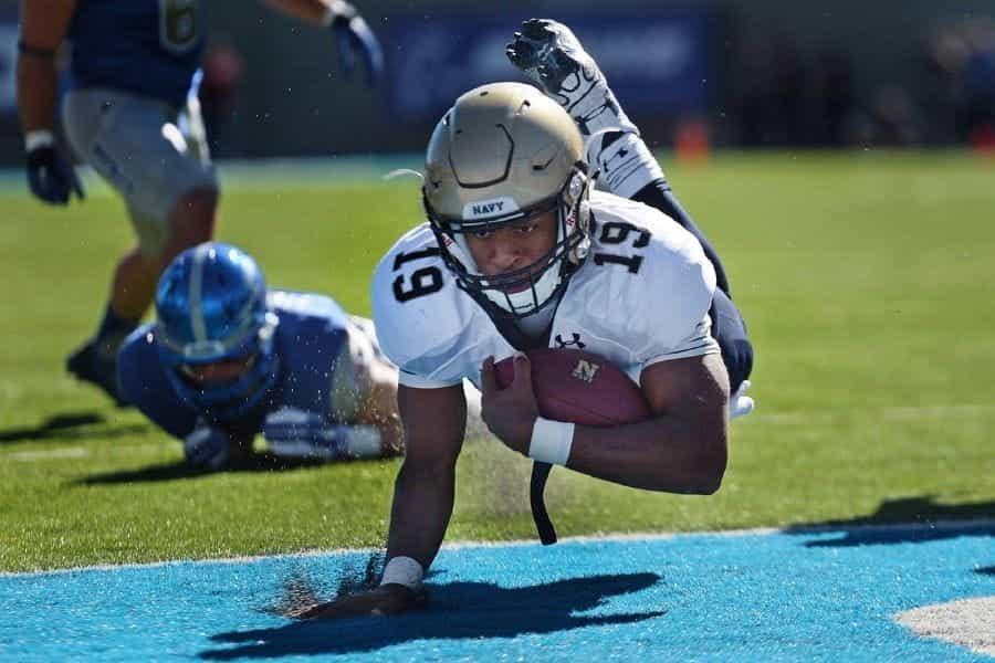 Seorang pemain sepak bola Amerika yang memegang bola meluncur ke arah touchdown.