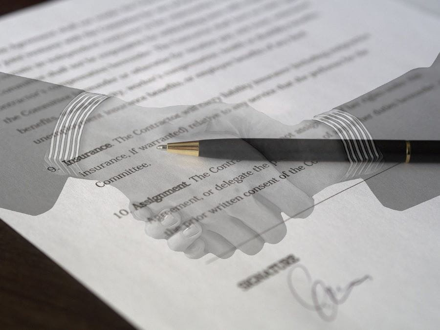 Two hands shake over a close-up view of a business contract.