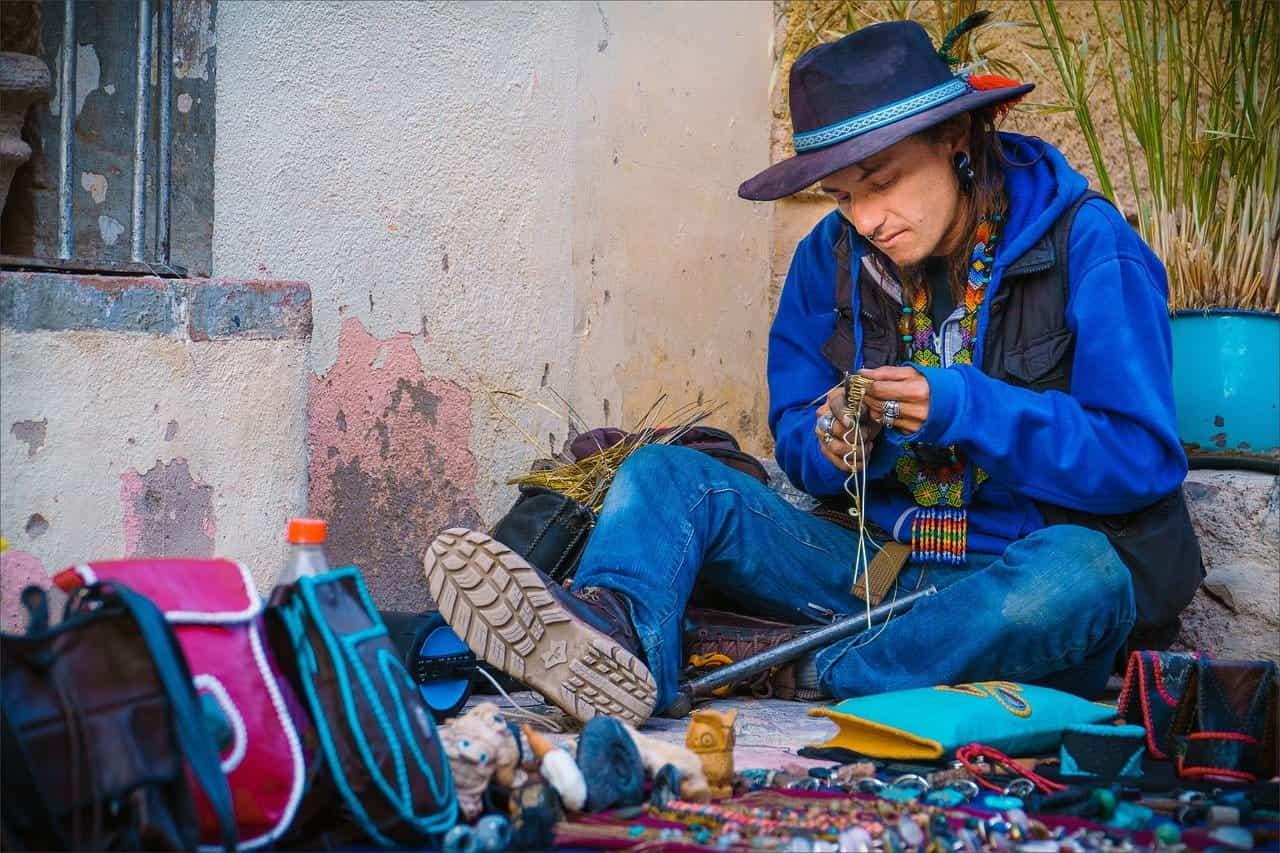 Seorang pria duduk di tanah membuat kerajinan kawat di Meksiko.
