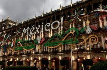 "A sparkly sign on an old building reads ""MEXICO!"" in white, green, and red."