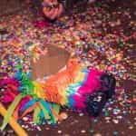 A smashed piñata lies on the ground.