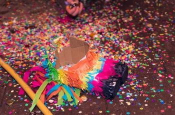 A smashed piñata lies on the ground.