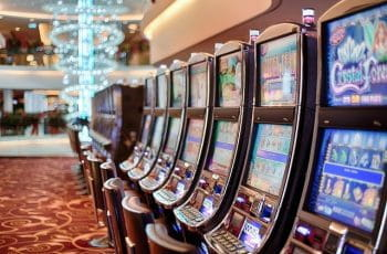 A row of slot machines in a brightly-lit casino.