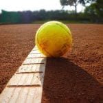 A tennis ball on the line of a clay court.