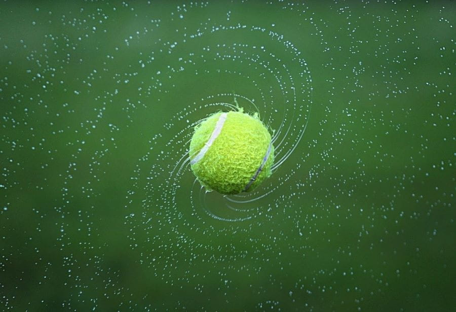 A wet tennis ball spinning and sending off droplets of water.