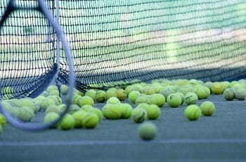 Many tennis balls next to the net on the court.