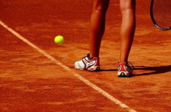 A tennis player preparing to serve in a game of tennis on a clay court.
