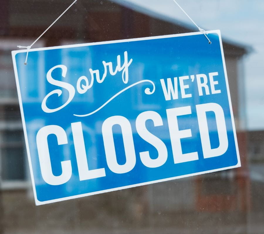 A blue sorry we're closed sign in a shop door.