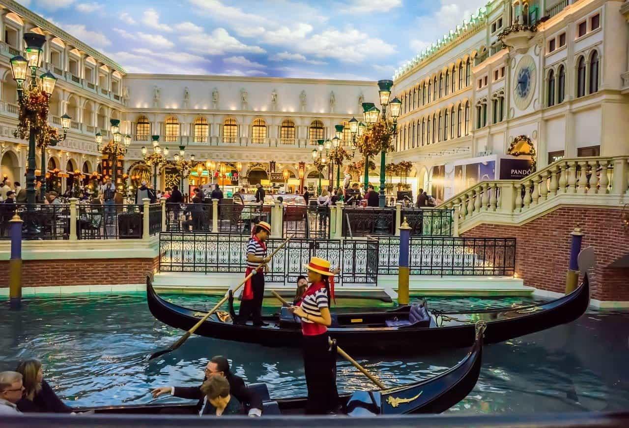 """Dua pendayung gondola melayang melewati sebuah """"luar ruangan"""" restoran di The Venetian di Las Vegas."""