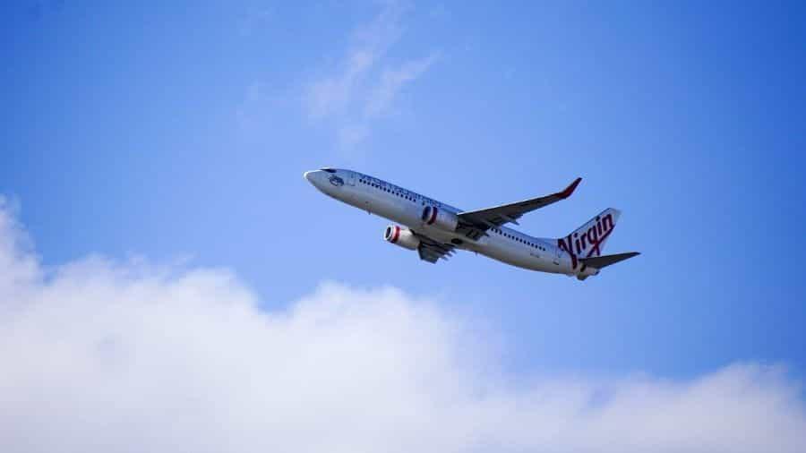 Sebuah pesawat Virgin Australia terbang tinggi di langit.