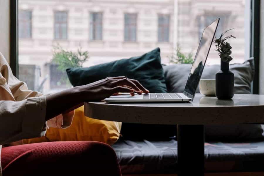 Seseorang sedang mengetik di laptop di meja kecil.