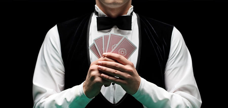 A man holding five playing cards.