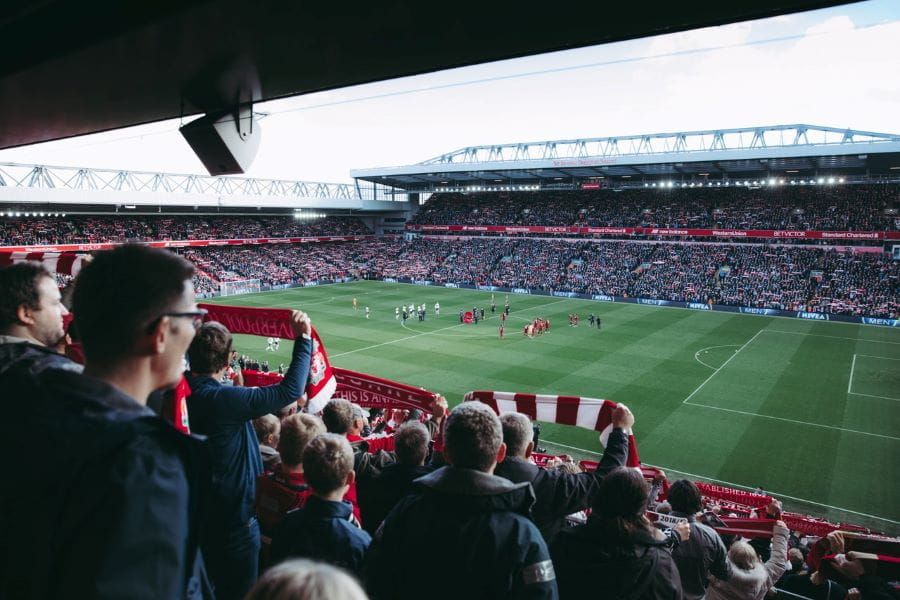 Kerumunan penggemar sepak bola Liverpool menonton pertandingan di stadion.