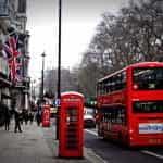 Kotak telepon merah dan bus di jalan London.