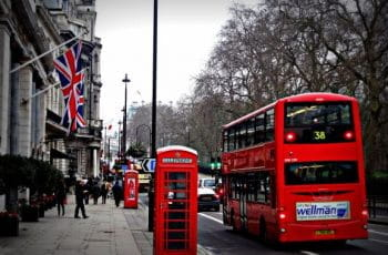 A red telephone box and a bus on a London street.