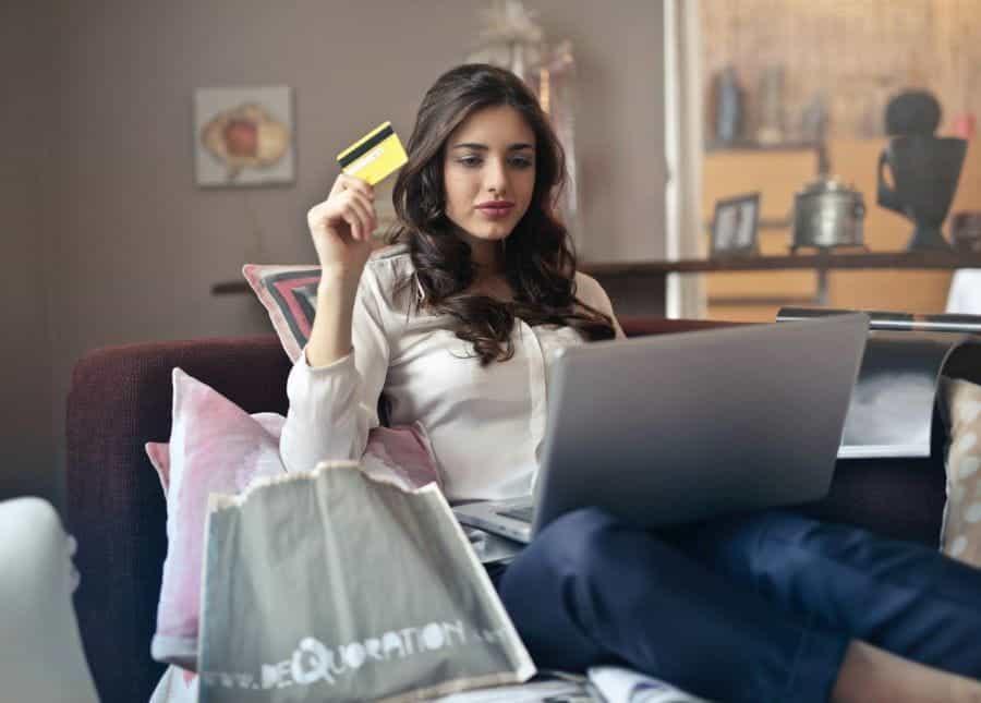 Seorang wanita yang memegang kartu kredit dan menggunakan laptop.