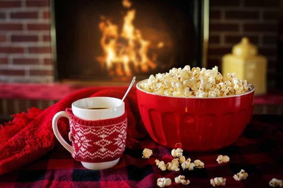 Secangkir cokelat panas dan semangkuk popcorn duduk di atas meja di depan api unggun.