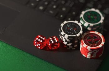 A pair of dice and three stacks of gambling chips resting on the open surface of a laptop computer.