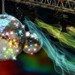 A gleaming disco ball in a dark and colorful club.