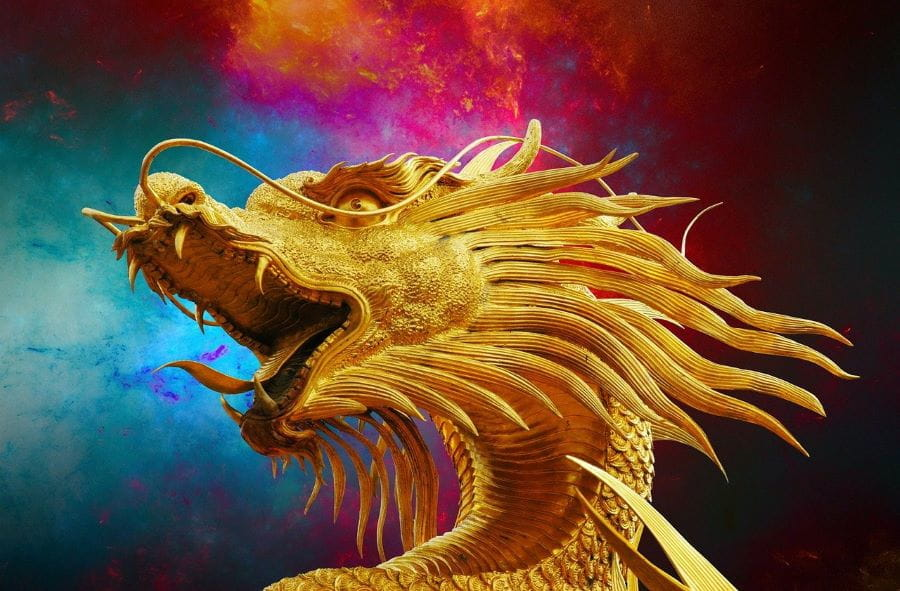 A golden statue of a roaring golden dragon in front of a colorful background.