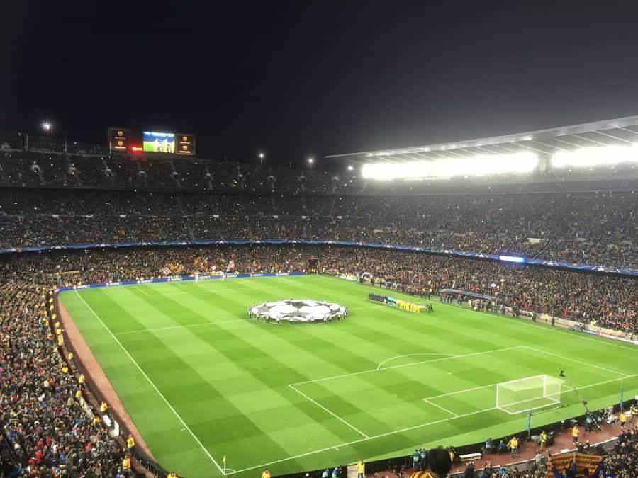 Stadion sepak bola yang diterangi di malam hari, dengan pemandangan lapangan saat kedua tim bersiap untuk kickoff.