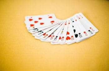 A deck of playing cards on a yellow background.