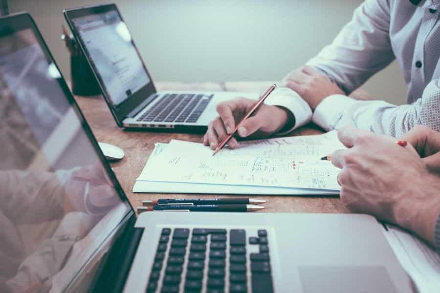 Dua pekerja kantor sedang mendiskusikan dokumen dengan laptop.