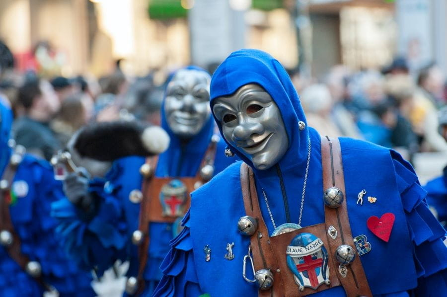 Orang-orang yang mengenakan kostum biru dan topeng perak berparade selama Mardi Gras di New Orleans, Louisiana.