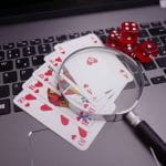 Satu set kartu dan dua pasang dadu diletakkan di atas laptop, dengan kaca pembesar ditempatkan di atas kartu.