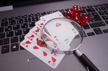 A set of cards and two pairs of dice resting atop a laptop, with a magnifying glass placed on top of the cards.