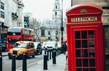 A red telephone box in London, with bus and taxis.
