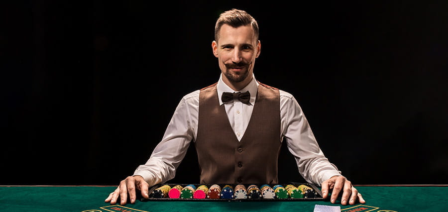 A croupier sitting at a table with casino chips and cards in front of him.