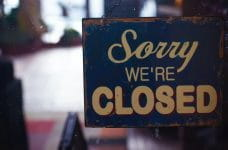 A blue shop sign that says sorry we're closed.