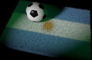 A soccer ball sits on grass emblazoned with the flag of Argentina.